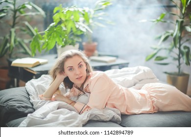 Morning leisure. Woman is lying on the bed