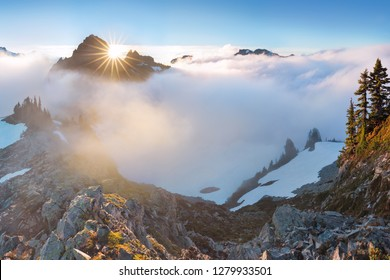 Morning light high above the cloud layer on Mount Rainier. Beautiful Paradise area, Washington state, USA in the fall with snow on Mount Rainier on a sunny day and morning with blue sky. Cascade Range
