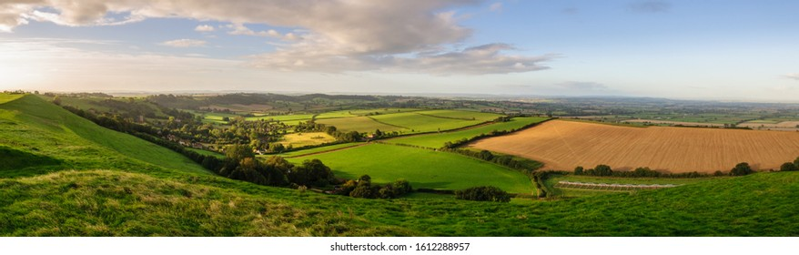 Morning light illuminates the landscape of the Somerset Levels viewed from Corton Beacon hill in South Somerset, England.