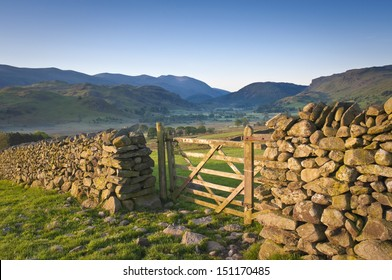 Morning light illuminating traditional dry stone wall, farmers gate in the  Lake District, Cumbria.