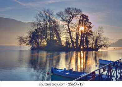 Morning light through the trees on a small island in lake Annecy France with small fishing boats tied up in the foreground.