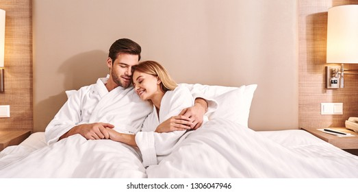 Morning with a loved one. Couple are hugging in hotel room bed