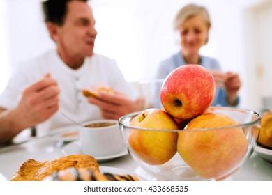 Morning meal. Senior man and woman having breakfast.