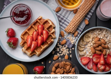 Morning meal set. Breakfast. Delicious oatmeal granola with berries, nuts and honey. A crispy waffle topped with strawberry jam. On a black table background. Top view