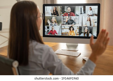 Morning meeting online. A young woman is using app on pc for connection with colleagues, employees. Video call with many people together. Back view