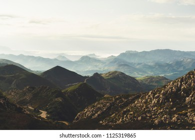 morning mist in the mountain peaks on natural landscape. Green valley on background foggy dramatic sky. Panorama horizon perspective view of scenery hills Spain mountain tops. Travel mockup concept