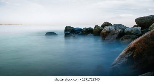 Morning mist over rocks and sea, Aarhus, Denmark, Europe