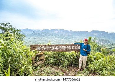 Morning mist and raining with travellers at viewpoint Doi Tapang, Chumphon, Thailand. Thai language is name of viewpoint Doi Tapang. Relaxation and travel concept.