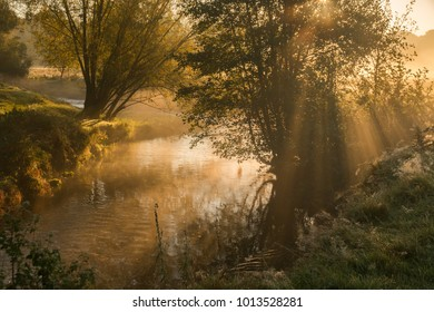 Morning mist and sunbeams over the river Geul
