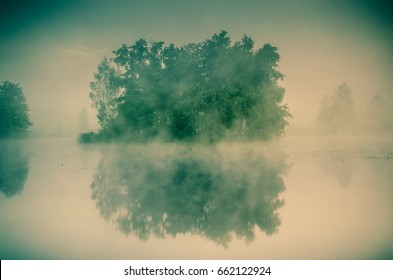 Morning misty landscape on the lake. Island with trees on the lake.