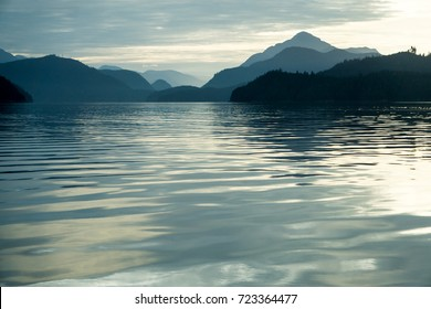 Morning Mood at Knight Inlet in Canada with sea and mountains in various blue tones and lots of copy space