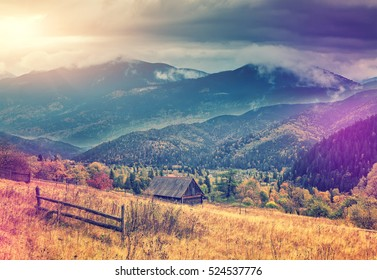 morning in the mountain village. wonderful rural landscape at sunrise.  majestic mountains with  overcast clouds. retro and vintage style. artistic creative image. instagram filter