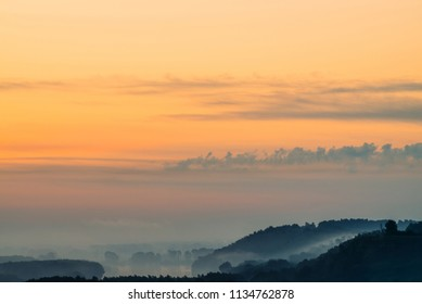Morning mystic haze above broad valley of river. Gold glow from dawn in sky. Riverbank with forest under fog. Sunlight reflected in water at sunrise. Colorful atmospheric landscape of majestic nature.