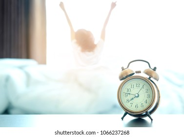 Morning of a new day, alarm clock wake up woman sitting on the best in the room. And she stretch the muscles at window. Health and care concepts