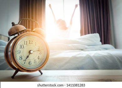 Morning of a new day, alarm clock wake up man sitting in the room. A woman stretch the muscles at window. Health and care concepts