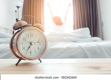 Morning of a new day, alarm clock wake up woman in the room. A woman stretch the muscles at window. Health concept.