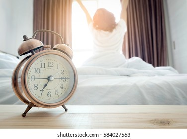 Morning of a new day, alarm clock wake up woman sitting in the room. A woman stretch the muscles at window. Health concept.