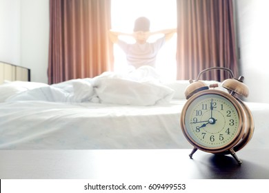 Morning of a new day, alarm clock  waking up man stretch the muscles  at window , . Health concept