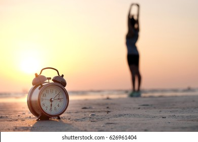Morning of a new day, alarm clock woman playing yoga and stretching muscles on the beach sunlight in morning.