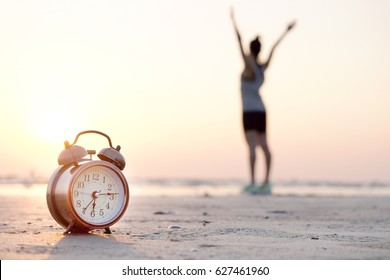 Morning of a new day, alarm clock  woman playing yoga and stretching muscles on the beach sunlight in morning. Health concept.