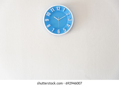 Morning, night or bed time with 10:10 clock on white concrete wall interior background with copy space, message board concept. 10 am is the late time in the morning. 10 pm is the bed time in the night