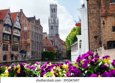 Morning in the old town with a river. Beautiful flowers on foreground. Bruges.