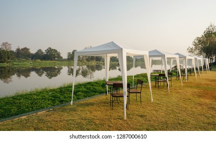 Morning on the Riverbank. On the bank of the river, there are a row of tents and tables.
