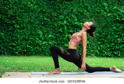 Morning outdoor garden grass green park natural holiday female model trainer slim fit sixpack body wear sport bra is playing yoga balance workout fitness class excercise for health care insurance