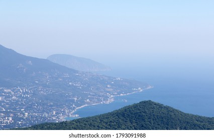 Morning over the Black sea from the height of mount AI-Petri.Yalta, Ayu-Dag in a haze of fog, mountain below, coastline, horizon line, no people. Space for text. Russia, Crimea,