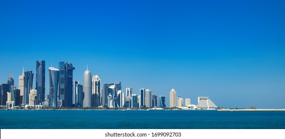 Morning panoramic cityscape view of Doha skyscrapers and towers from Persian Gulf. Futuristic skyline of financial commercial district in Qatar on horizon