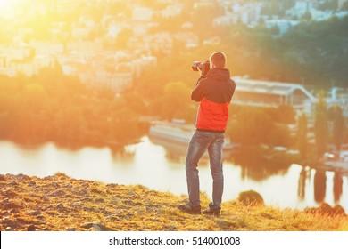 Morning photo shooting. Photographer with mirror camera taking photo of the amazing sunrise.