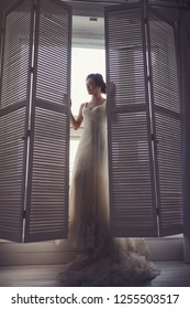 morning portrait of the bride in a wedding dress near the window