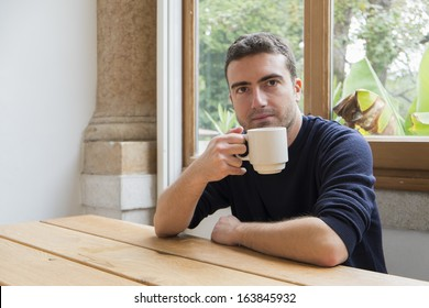 morning portrait of a guy holding coffee cup.
