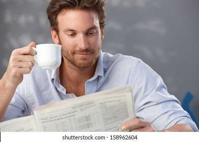 Morning portrait of handsome guy reading newspaper and holding coffee cup.