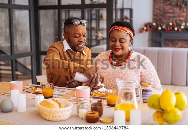 In the morning. Positive joyful couple sitting at the table while having breakfast together