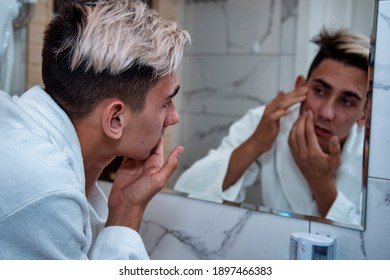 Morning procedures in the bathroom. A young man in a white coat stands at the mirror. Problem skin and care for it. Non-standard appearance.