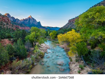 Morning rays illuminate fall colors along the Virgin River and Watchman Peak, Zion National Park, Utah