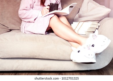 morning reading with cup of coffee home woman sitting on a couch wearing pink bathrobe and fluffy slipers unicorn