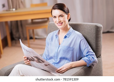 Morning reading. Prosperous budding beautiful woman relaxing in the armchair while holding newspapers and grinning to the camera