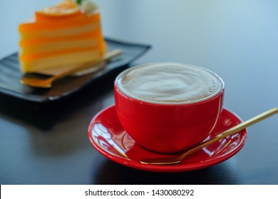 Morning red cup cappuccino coffee and orange cake background