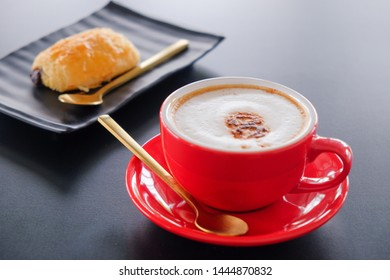 Morning red cup​ cappuccino​ coffee​ on black table​ and bakery background