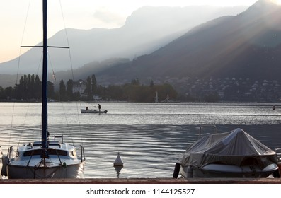 in the morning, rising sun behind the mountains surrounding Lake Annecy, a fisherman in the background on his boat and in the foreground of the dockside