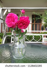 morning roses in the clear jar is on the table with background of two hearts designed of swing chair