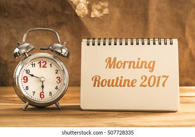 morning routine 2017 text on notebook with alarm clock on wood table.