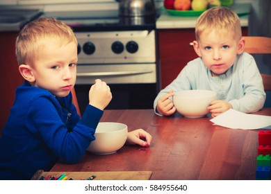 Morning routine in family, healthy diet for children concept. Two boys, kids eating breakfast together.