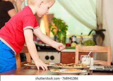 Morning routine in family, healthy diet for children concept. Little boy preparing pancakes for breaktfast