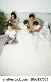 Morning routine. Happy latin family with cute little kids starts morning together. Loving parents spending time, playing with their children, staying in bed