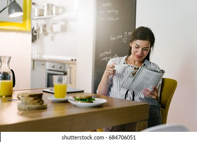 Morning routine. Woman reading newspaper during breakfast at her home