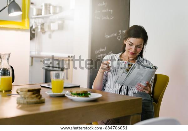 朝の日課。自宅で朝食中に新聞を読む女性