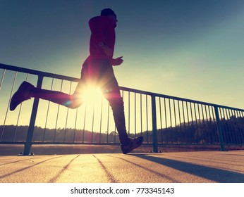 Morning runner in tall black leggings exercising  on bridge. Outdoor exercising on smooth concrete ground on lake bridge. Sun is outlining man body